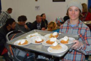 Volunteer serving Thanksgiving dinner